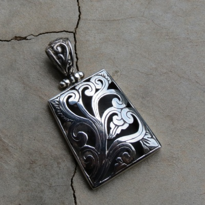 silver rectangular pendant with swirl design