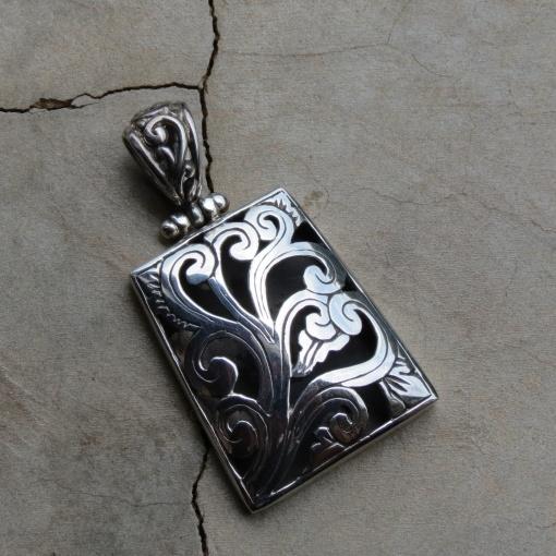 silver rectangular pendant with swirl design